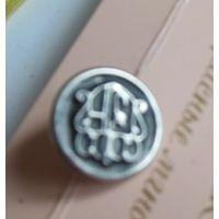 Пуговица металлическая со странной символикой.