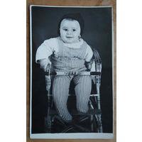 Ребенок на стульчике. Фото 1970-х. 8.5х14 см.
