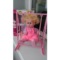 Кукла  на качелях качающаяся под музыку